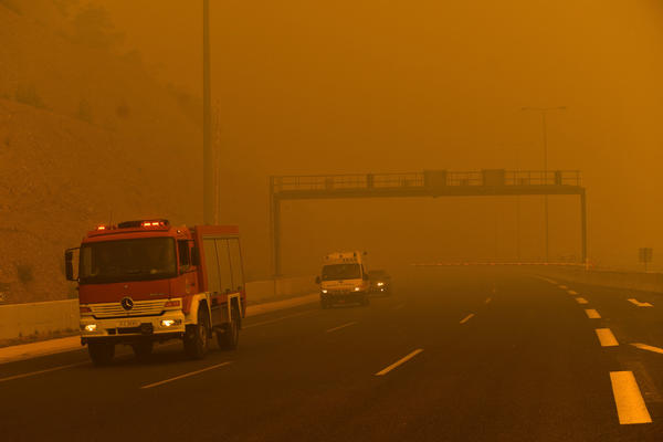 A firefighting truck drives through a haze of smoke as a wildfire burns Monday in Kineta.