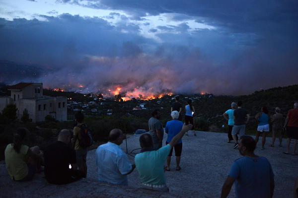 People watch a wildfire in the town of Rafina on Monday.