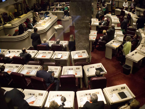 State representatives work in the house chambers at the State House in Montgomery, Ala. A federal appeals court sided with workers from Birmingham, Ala., who argued that state lawmakers racially discriminated against the majority-black city by blocking a minimum wage hike.