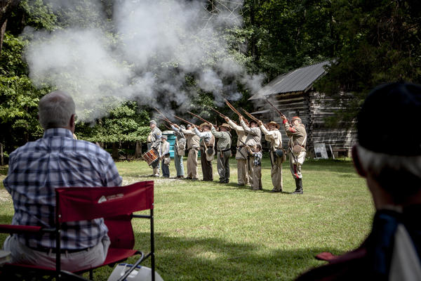 Civil War re-enactors representing members of the Confederate army's 9th Mississippi and 51st Tennessee infantries deliver a musket salute.