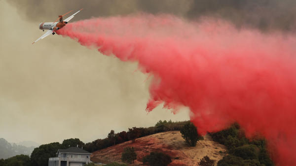 A plane drops retardant over a property threatened by a wildfire, on Monday in Lakeport, Calif.