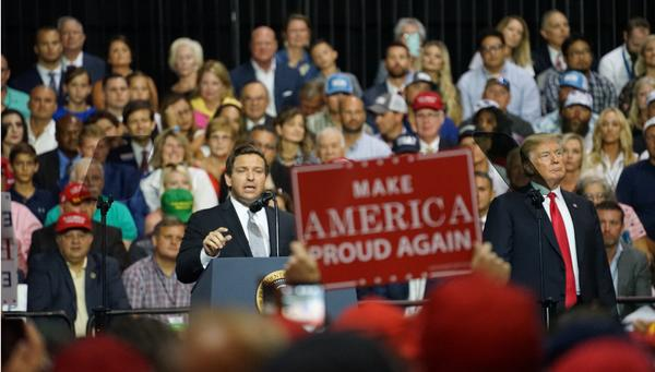 Rep. Ron DeSantis, left, speaks after President Donald Trump formally endorsed him for the GOP nomination for Florida Governor at a July 31, 2018 rally at the Florida State Fairgrounds in Tampa.
