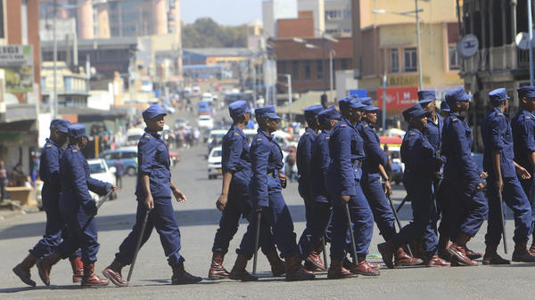 Zimbabwean police patrolled the streets of the capital, Harare, on Thursday. Police said six people died when army troops opened fire on protesters the day before.