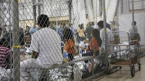 In this June 17, 2018 file photo provided by U.S. Customs and Border Protection, people who've been taken into custody on charges of illegal entry sit in cages at a facility in McAllen, Texas.