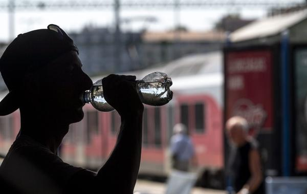 A man drinks water distributed free to passengers of the Hungarian State Railways at the Deli Railway Station in Budapest, Hungary, Monday, July 30, 2018, as the highest daytime temperature may reach 35 degrees Celsius (95 degrees Fahrenheit) in most parts of the country, and the highest degree heat alert has been issued by the Hungarian health authority. (Zsolt Szigetvary/MTI via AP)