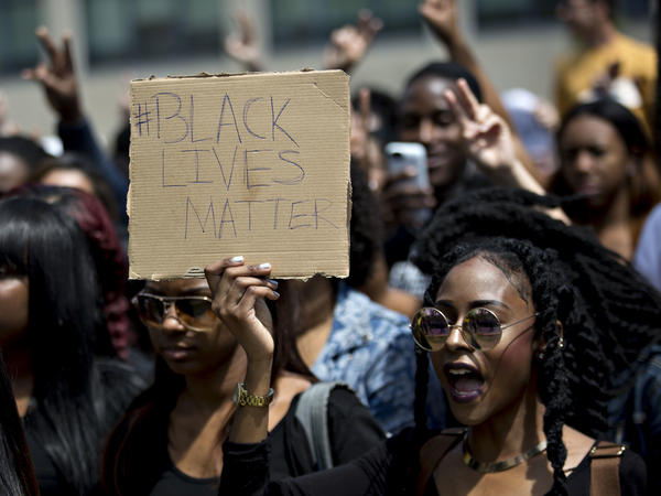 """A demonstrator holds a """"Black Lives Matter"""" sign while protesting then-presidential candidate Donald Trump in 2016. The hashtag started five years ago and is an """"archetypal"""" example of a hashtag tied to political issues or causes."""