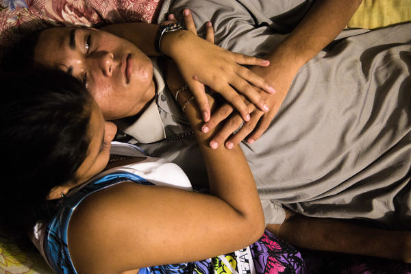 Moises and his girlfriend, Cindi, discuss their future. When Ayuso took this photo, she had just told Moises that she is pregnant. They discussed their options; Moises said he would consider migrating to save himself from gang violence — and be able to make money for the child.