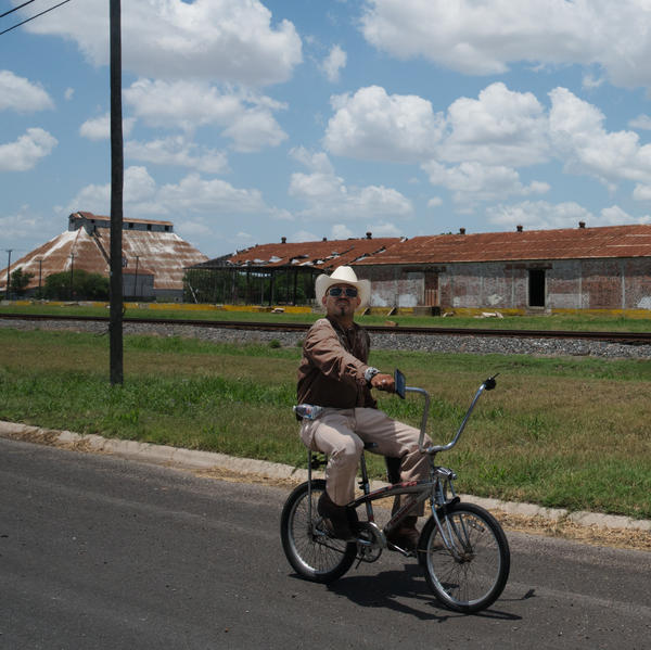 A man rides his bike on one of the main streets in Raymondville, TX.
