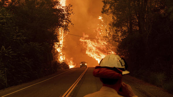 A car passes through flames on Highway 299 as the Carr Fire burns through Shasta, Calif., on July 26. Fueled by high temperatures, wind and low humidity, the blaze has destroyed multiple structures and killed seven people.