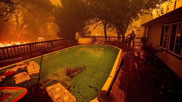 A firefighter gathers water from a pool while battling the Ranch Fire near Clearlake Oaks, Calif., on Saturday.