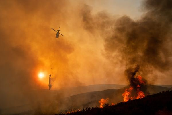 A helicopter drops water while battling the Ranch Fire, part of the Mendocino Complex Fire, near Clearlake Oaks, Calif., on Sunday.