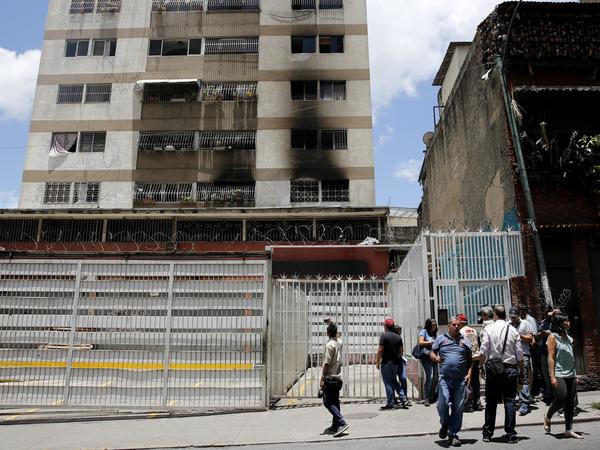 Members of the media circulate outside an apartment complex where an allegedly armed drone crashed Saturday in Caracas, interrupting President Nicolas Maduro's speech.