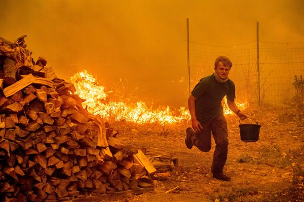 Alex Schenck carries a water bucket while fighting to save his home near Clearlake Oaks, Calif. on Saturday, as the Ranch Fire approached.