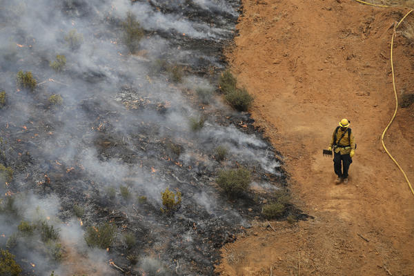 A firefighter walks along a containment line while battling a wildfire in Redding, Calif., on July 28.