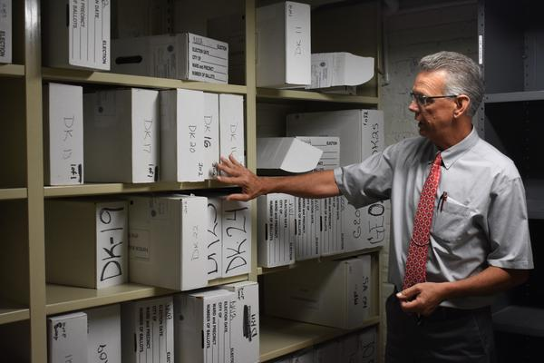 DeKalb County Clerk and Recorder Doug Johnson stands in front of marked boxes that hold original paper ballots from the 2016 general election. Boxes are separated by precinct.