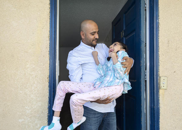 Nageeb Alomari holds his 10-year-old daughter, Shaema, in their front doorway just as he did outside the U.S. Embassy in Djibouti. Nageeb is from Yemen, but became an American citizen in 2010, and later applied for visas for his wife and daughters. Because Shaema is unable to walk on her own, Nageeb carried her to the family's appointment at the embassy.