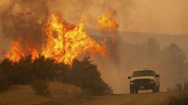 A truck passes by flames from the Ranch Fire in Clearlake Oaks, Calif., on Sunday.