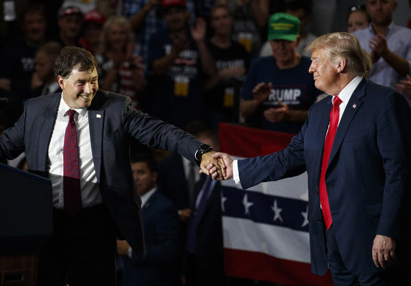12th Congressional District Republican candidate Troy Balderson, left, reaches for President Donald Trump as he speaks at a rally at Olentangy Orange High School in Lewis Center, Ohio, Saturday, Aug. 4, 2018.
