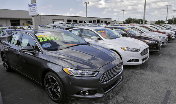 A car salesman works the telephone while searching through inventory at the certified used car lot at Brandon Ford in Brandon, Fla. (Chris O'Meara/AP)