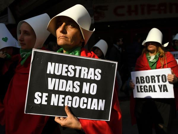 Abortion-rights supporters demonstrate earlier this month outside the National Congress in Buenos Aires, adding the legalization campaign's distinctive green handkerchiefs to outfits alluding to the dystopian novel <em>The Handmaid's Tale</em>. The book's author, Margaret Atwood, has said she drew inspiration from Argentine history.