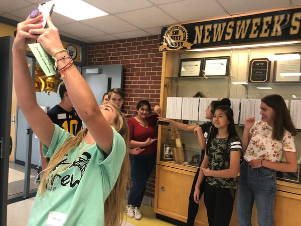Junior Phoenix Bialek takes a selfie with the freshmen she's leading on a scavenger hunt around Shawnee Mission West High School.