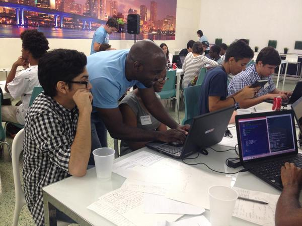 "Instructor Kareem Green works with students at a ""CodeNow"" coding camp in Miami in June 2014."