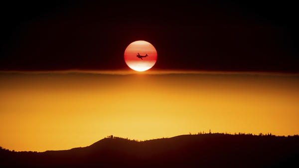 A plane battling the Ferguson Fire passes the setting sun in unincorporated Mariposa County Calif., near Yosemite National Park in July 2018.