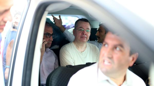 Andrew Craig Brunson, a U.S. pastor on trial for espionage in Turkey, sits in the backseat of a vehicle squeezed between two Turkish plainclothes police officers late last month. The minister's nearly two-year detention has become a flashpoint of friction between the two allies.