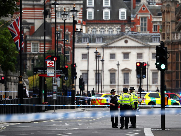 Police stand in the street after a car crashed outside the Houses of Parliament in Westminster, London, on Tuesday.