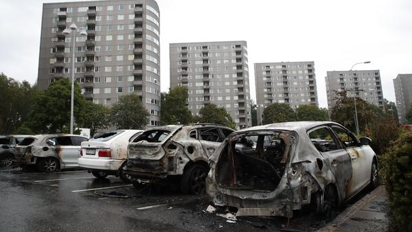 Burned cars are pictured at Froelunda Square in Gothenburg, Sweden, on Tuesday. Up to 80 cars have been set on fire in western Sweden by masked vandals, police say.