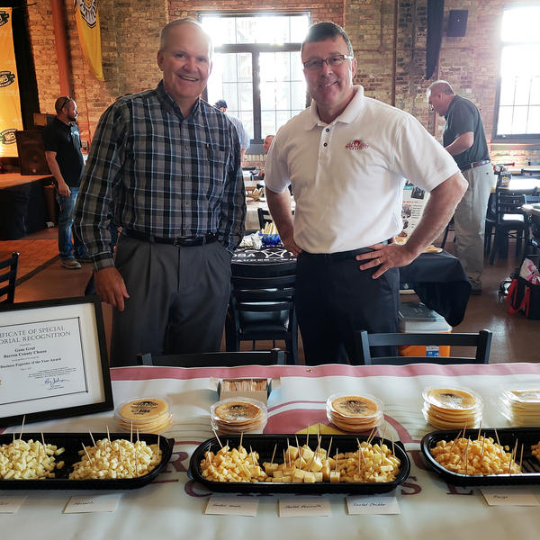 Gene Graf (right) and David Kochendorfer (left) of Barron County Cheese behind their cheese table at a Wisconsin event promoting cheese for export.