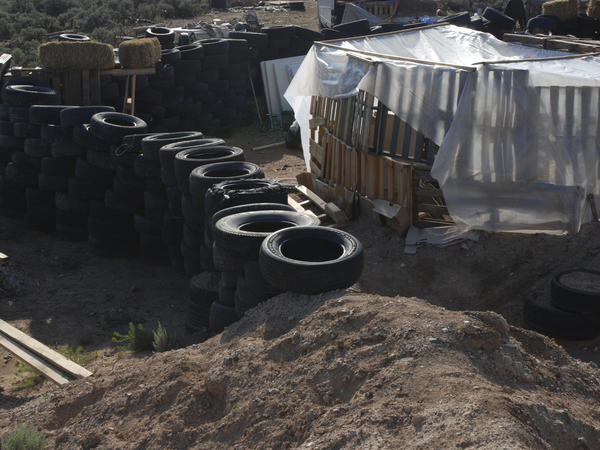 Tires form a wall at the squalid makeshift living compound where five adults were arrested on child abuse charges and the remains of a boy were found.