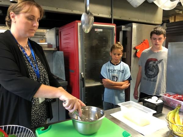 Two seventh grade students at Center Middle School watch as cooks scramble eggs for protein-rich breakfasts.