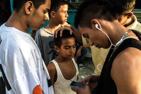 A group of older boys, some of whom are gang members, joke around with a younger boy. Neighborhood children are often groomed for gang activity from the age of 6 or 7. At first they may be given small assignments — like buying snacks for gang members or monitoring who's coming in and out of a neighborhood, says Ayuso. Bit by bit, he says, they graduate into bigger responsibilities.