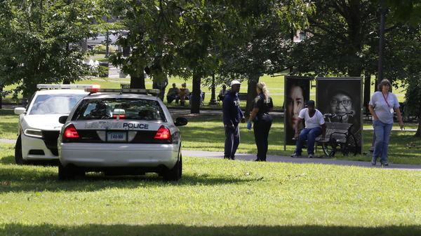 A police officer speaks to a man on New Haven Green, where more than 70 people fell ill from suspected drug overdoses on Wednesday in New Haven, Conn.