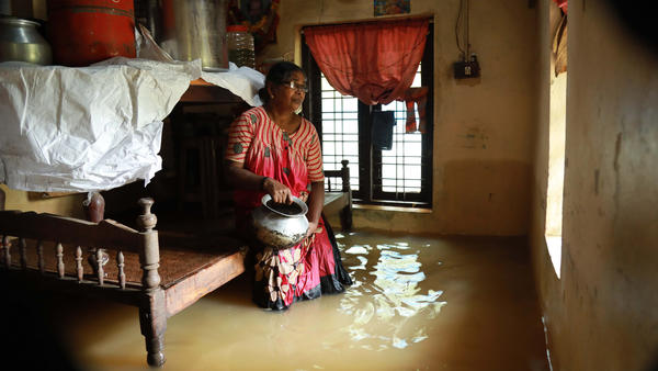 An Indian woman watches as the floodwaters rise inside her house earlier this month in Kochi, in the Indian state of Kerala.