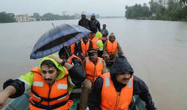 Indian fire and rescue personnel evacuate local residents from their homes in Aluva, Kerala, on Thursday. About 85,000 people have been displaced in the southern state of Kerala.
