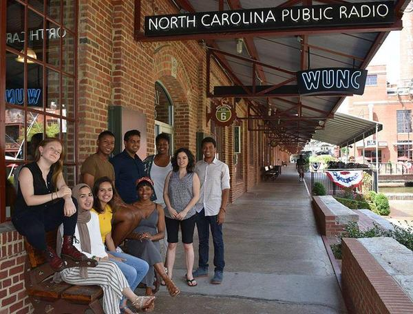 The 2018 cohort of youth reporters pose outside of WUNC's downtown Durham studios with lead mentors Kamaya Truitt-Martin and Allison Swaim.