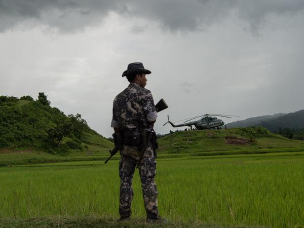 A member of the Myanmar security forces stands guard near a military transport helicopter in Rakhine state last September, about a month into the bloody crackdown on the country's Rohingya Muslim population.