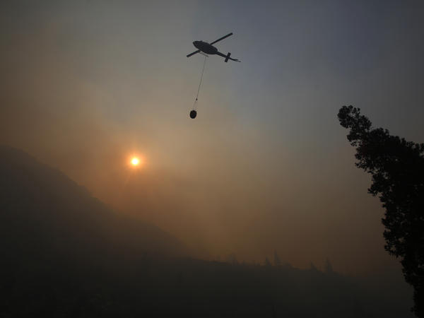A fire helicopter takes off through smoke rising to make a drop on active fires in Yosemite National Park last week after the park reopened following  a three-week closure.