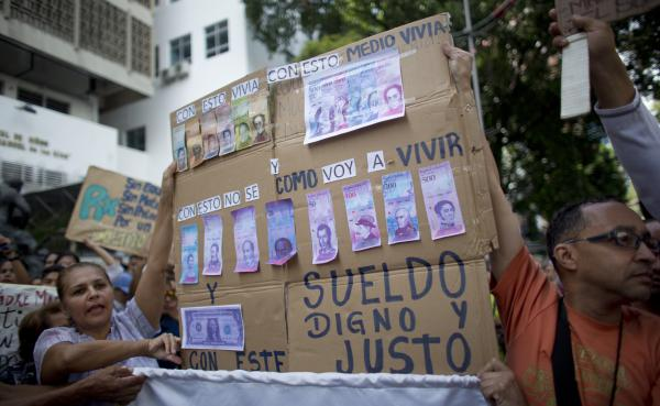 Nurses present a sign with fake currency on it, showing how badly nurses' salaries have been devalued by inflation, during anti-Maduro protests last week in Caracas.