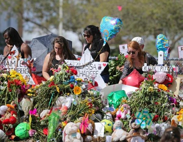 Mourners gather at on-campus memorials for the 17 victims of the Marjory Stoneman Douglas High School shooting upon returning to campus in late February. Students' testimonials will be included in a new book.