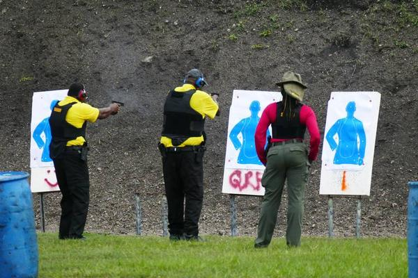 A Broward Sheriff's Office instructor, far right, oversees two of the armed guardian trainees during a firearms training at the BSO shooting range at Markham Park on July 30.