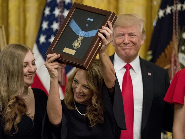 Valerie Nessel (second from left), accompanied by family members, accepts the Medal of Honor from President Trump awarded posthumously to her husband, Air Force Tech. Sgt. John A. Chapman.