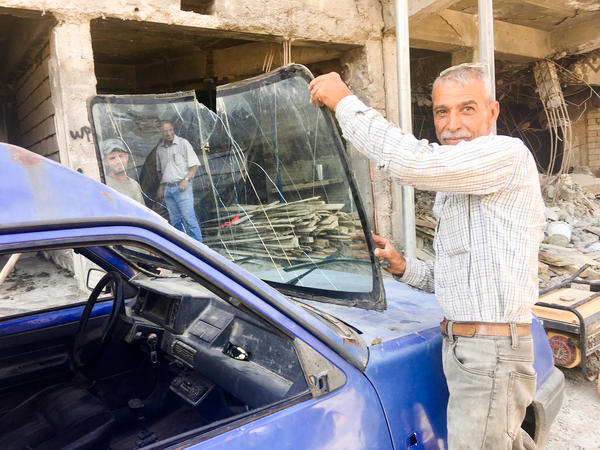 Ghanem Saleh, who leads a renovation crew repairing shops on a market street in Mosul's Old City, pulls out the windshield of his car. It was damaged when an airstrike hit the building behind him, where ISIS had parked a car bomb.