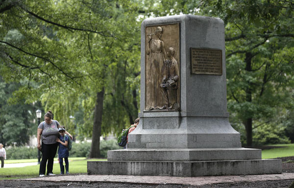 People gather near the remaining monument following a Monday night rally where the Confederate statue known as Silent Sam was toppled from it's pedestal by protesters at the University of North Carolina in Chapel Hill, N.C., Tuesday, Aug. 21, 2018.