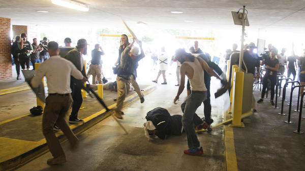 DeAndre Harris, crumpled on the ground, is beaten by several men in a parking garage beside the police station in Charlottesville, Va., shortly after a white nationalist rally in August 2017.