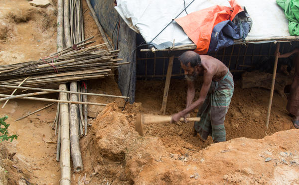 Rohingya refugee Shah Miya digs at the sand that inundated his shelter.  Despite the threat of more landslides, he says he doesn't want to move.