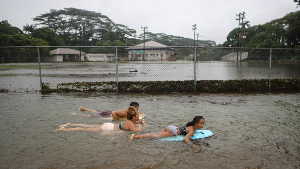 People bodyboard in floodwaters at a baseball field in Hilo, Hawaii, on Saturday after Hurricane Lane — now a tropical depression — drenched much of the state. The rainfall set a record at Hilo International Airport.