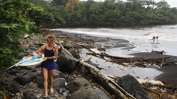 A surfer leaves the beach at Honoli'i Beach Park in Hilo, Hawaii, walking through the remains of trees that were swept away by floodwaters from Hurricane Lane. Now a tropical storm, Lane brought heavy rains to Hawaii before it weakened.